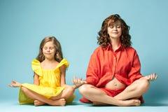 Mère enceinte avec la fille de l'adolescence Portrait de studio de famille au-dessus de fond bleu Image libre de droits