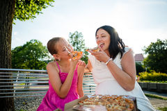 Mère enceinte avec sa fille mangeant de la pizza ensemble image stock