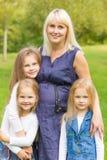 Mère enceinte de jeunes avec ses filles en parc Images stock