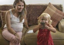 Mère enceinte de jeunes regardant la fille payant avec le cellul photographie stock