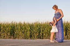 Mère enceinte et sa fille entre les champs de maïs Images stock