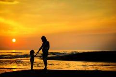 Mère enceinte et un enfant par la mer Photo stock