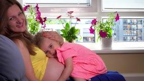 Mère enceinte heureuse et embrassement et regard mignons de fille à l'appareil-photo avec le sourire banque de vidéos