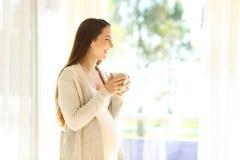 Mère enceinte regardant loin par une fenêtre Photo stock