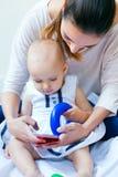 Mère et bébé à l'aide d'un smartphone à la maison Photos stock