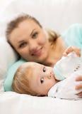Mère et bébé adorable avec l'alimenter-bouteille photographie stock
