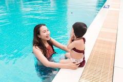 Mère et bébé ayant l'amusement dans la piscine Vacances d'été et Photos libres de droits