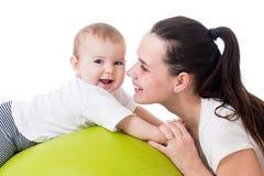 Mère et bébé ayant l'amusement sur la boule gymnastique Photo stock