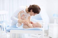 Mère et bébé dans la couche-culotte sur la table changeante photographie stock libre de droits