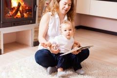 Mère et bébé garçon s'asseyant près de la lecture de cheminée Photos libres de droits
