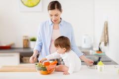 Mère et bébé heureux avec la cuisine de nourriture à la maison Image stock