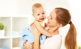 Mère et bébé heureux de famille dans une serviette bleue après s'être baigné Photos stock