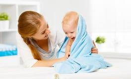 Mère et bébé heureux de famille dans une serviette bleue après s'être baigné Photographie stock libre de droits