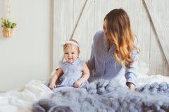 Mère et bébé heureux de bébé de 9 mois dans des pyjamas assortis jouant dans la chambre à coucher pendant le matin Photos stock