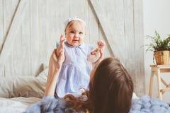 Mère et bébé heureux de bébé de 9 mois dans des pyjamas assortis jouant dans la chambre à coucher pendant le matin Photographie stock