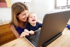 Mère et bébé heureux employant l'ordinateur portable et le sourire Photos stock
