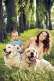 Mère et bébé jouant avec des animaux familiers Photo stock