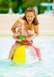 Mère et bébé jouant avec du ballon de plage dans la piscine Photos libres de droits