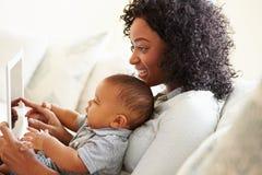 Mère et bébé jouant avec la Tablette de Digital à la maison Photo libre de droits