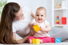 Mère et bébé jouant avec les jouets développementaux de couleur dans la crèche Photos libres de droits