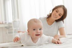 Mère et bébé jouant et souriant sur le lit Photos libres de droits