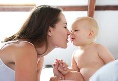 Mère et bébé jouant sur le lit photographie stock