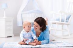 Mère et bébé jouant sur le plancher Photographie stock