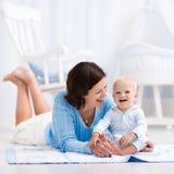 Mère et bébé jouant sur le plancher Photo stock