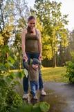 Mère et bébé marchant en parc Premières étapes de petit garçon drôle Photo stock