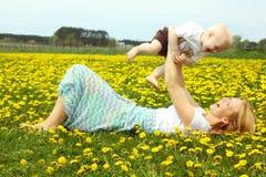 Mère et bébé riant en pissenlits Photos libres de droits