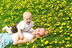Mère et bébé s'étendant en pissenlits Photos stock