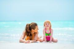 Mère et bébé s'étendant sur la plage Photo stock