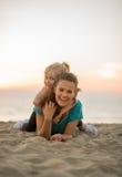 Mère et bébé s'étendant sur la plage Photos stock