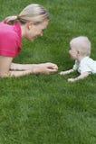 Mère et bébé se trouvant sur la pelouse Image libre de droits