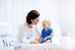 Mère et bébé sur la table changeante Photographie stock