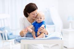 Mère et bébé sur la table changeante Photographie stock libre de droits