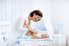 Mère et bébé sur la table changeante Photo stock