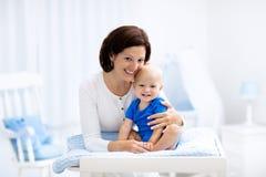 Mère et bébé sur la table changeante Images stock