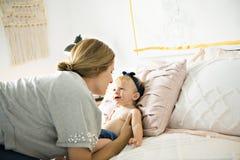Mère et bébé sur un lit blanc photographie stock libre de droits