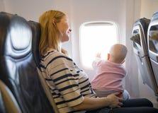Mère et bébé voyageant sur l'avion Image stock