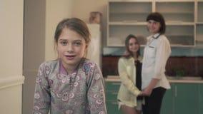 Mère et caresse plus ancienne de fille dans la cuisine à la maison Fille de Lillte dans le sourire de premier plan à la caméra banque de vidéos