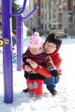 Mère et chéri à jouer dans la neige Photo stock