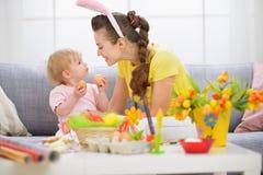Mère et chéri jouant avec des oeufs de pâques Image stock