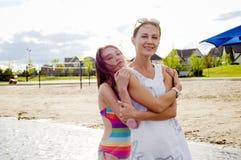 Mère et descendant à l'embrassement de plage Image stock