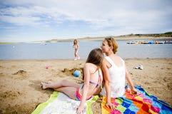 Mère et descendant à la plage parlant 2 Photographie stock