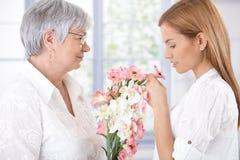 Mère et descendant aînés avec des fleurs Images stock