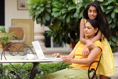 Mère et descendant affectueux avec l'ordinateur portatif à l'extérieur Image stock