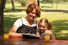 Mère et descendant affichant un livre Photographie stock libre de droits
