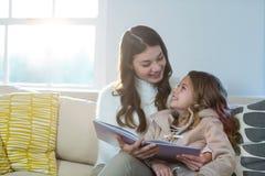 Mère et descendant affichant un livre Photographie stock
