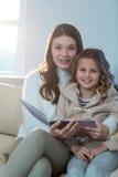 Mère et descendant affichant un livre Photos stock